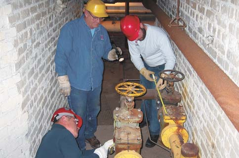 Glenn Bear, center, and Charlie Griesen, right, of Utility Services help measure the valve of a steam pipe that runs...