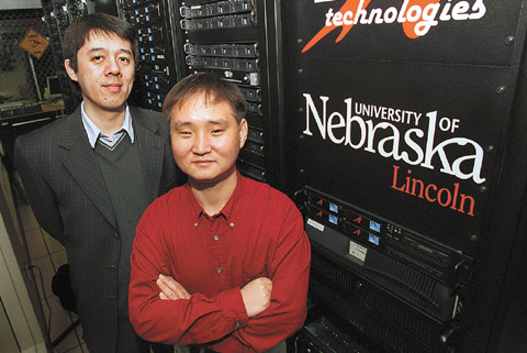 UNL Chemist Xiao Cheng Zeng, left, and graduate student Jail Bai stand next to UNL's supercomputer PrairieFire, which helped them...