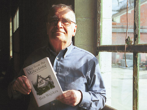 Lou Leviticus, professor emeritus and volunteer curator at the Larsen Tractor Museum on East Campus, holds a copy of his...