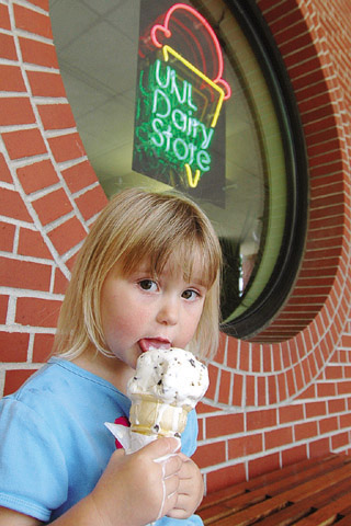 Norah Blow of Lincoln tries to eat her chocolate chip ice cream cone before it melts July 9 at UNL's...