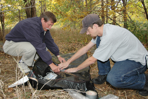 Entomologist Fred Baxendale, left, and Tim Huntington, an entomology graduate student, attach temperature-reading equipment to a body bag that contains...