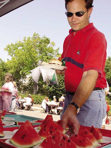 Gary Kimminau, assistant manager of Information Services, takes a slice of watermelon at the all-university picnic, which followed Chancellor Harvey...