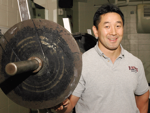 Shinya Takahashi, coordinator for strength and conditioning at UNL Campus Recreation, stands next to a set of free weights. A...
