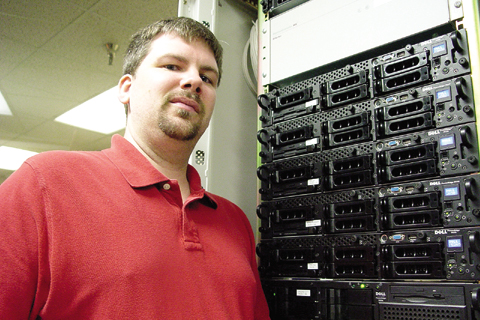 Zac Reimer, network security analyst for Information Services, stands next to a handful of the servers that handle e-mail traffic...