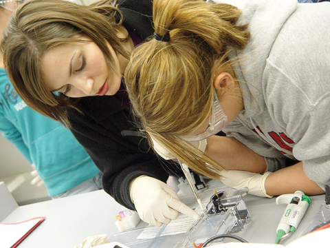 HANDS ON LESSON - Sarah Zulkoski-Benson, science outreach coordinator for the Center for Biotechnology, explains to Andrea Beyersdorf, Lincoln Southeast senior...