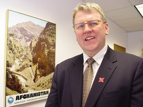 PEACE CORPS VOLUNTEER - Dave Wilson, associate vice chancellor for academic affairs, stands next to an Afghanistan poster in his office...