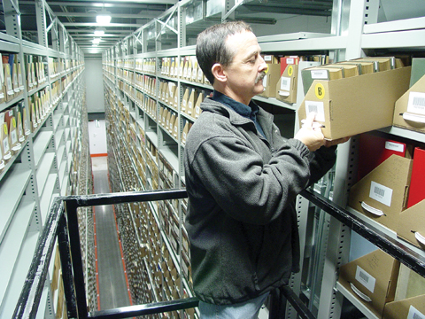 TALL ORDER - Gary Dolan looks for a book 30 feet in the air at the Library Depository/Retrieval Facility on...