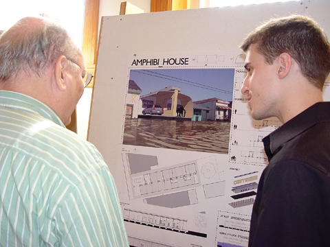 HOUSE TALK - Jason Cave (right), a senior architecture major from Omaha, discusses his Amphibi_House design with Ted Ertl, associate...