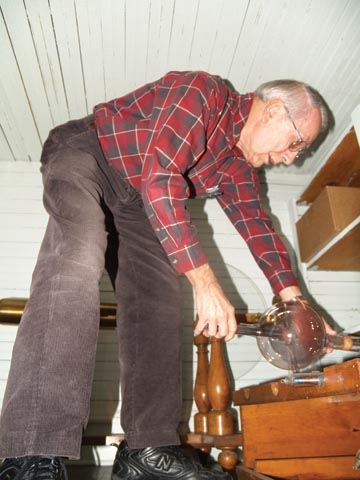 ATTIC FIND - Eugene Rudd examines an X-ray tube in one of the Brace Hall storage closets used to house the...