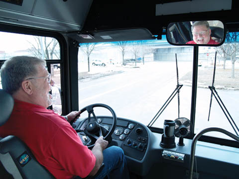 COMING AROUND - Gene Giles laughs at a stop along the garage bus route offered by Parking and Transit Services. A...