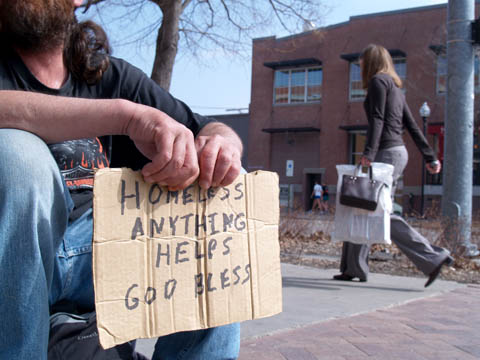CARDBOARD REQUEST - Tim, a 44-year-old homeless man, holds a cardboard sign as an individual walks by in downtown Lincoln...