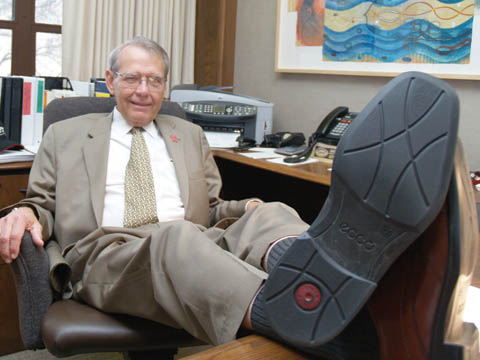 KICKING BACK - Herb Howe, associate to the chancellor, rests behind Chancellor Harvey Perlman's desk. After 38 years of service to...