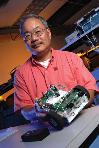 SPIRIT LEADER - Bing Chen, professor and chair of the Department of Computer and Electronics Engineering, holds a TekBot, a small...