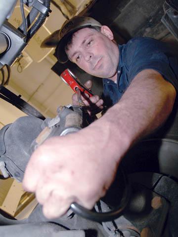 PREVENTATIVE MAINTENANCE - John Salzman, an ASE-certified diesel mechanic who works half-time for Transportation Services, lubes the NET remote satellite truck...