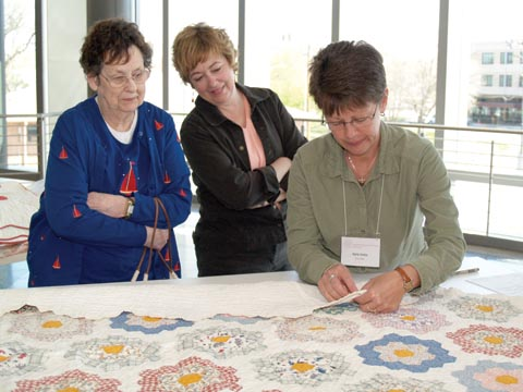 QUILT STUDY - (From left) Beulah and Laurie Bellows watch as Karla Salda, an IQSC volunteer, sews a muslin documentation label...