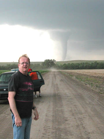 STORM MOMENT - Ken Dewey poses for a photo with a tornado during a May 29 storm chase in central Nebraska...