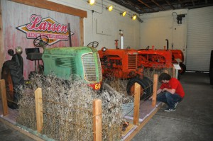 Lance Todd, manager of exhibits at the Lester F. Larsen Tractor Test and Power Museum, installs grass in a new exhibit. The project showcases an Oliver 60 and SC-Case in a setting that resembles an overgrown grass area behind a barn.